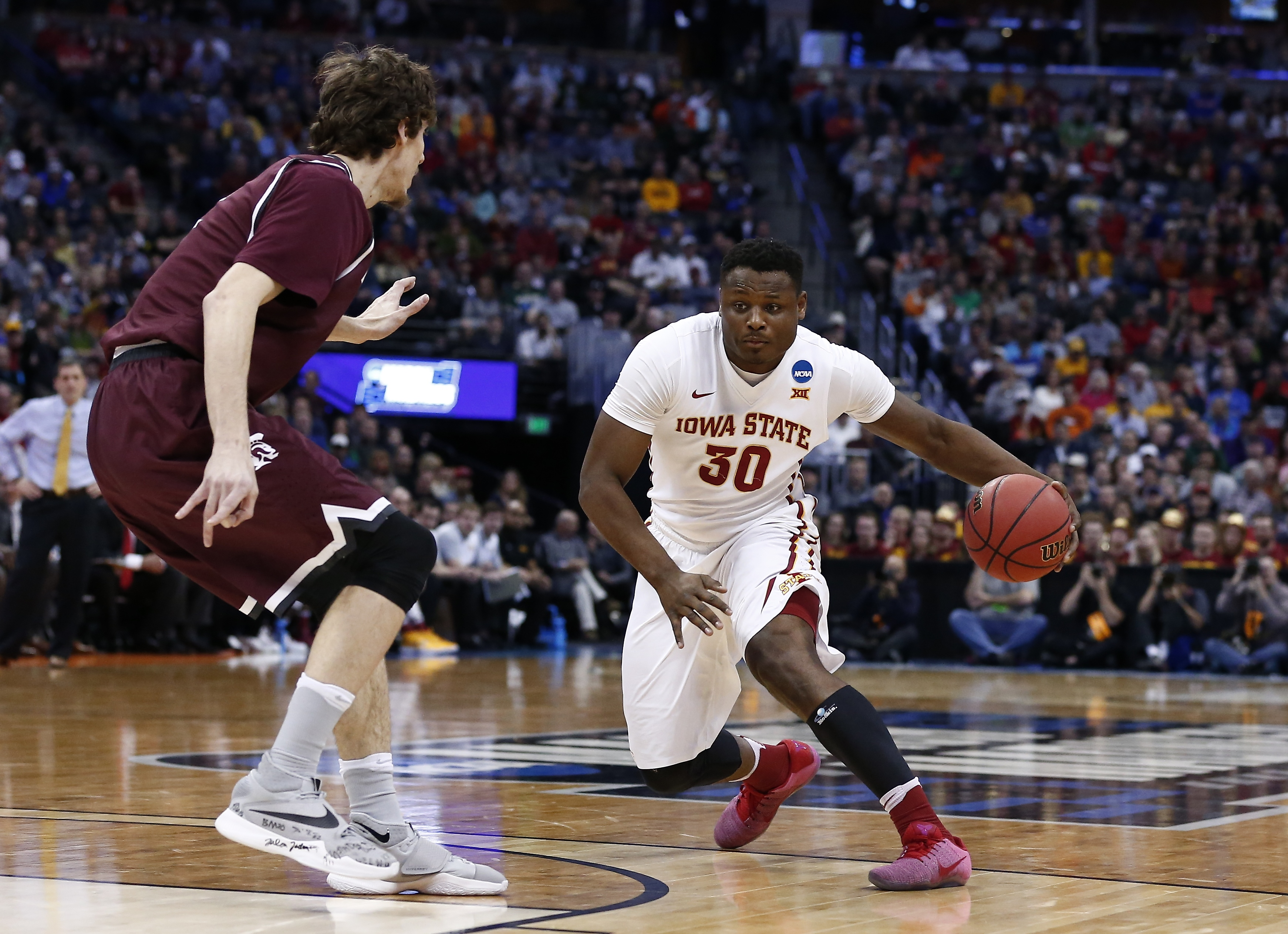 Mar 19, 2016; Denver , CO, USA; Arkansas Little Rock Trojans forward Lis Shoshi (12) defends as Iowa State Cyclones guard Deonte Burton (30) drives in first half action of Iowa State vs Arkansas Little Rock during the second round of the 2016 NCAA Tournament at Pepsi Center. Mandatory Credit: Isaiah J. Downing-USA TODAY Sports